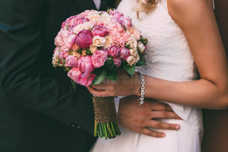 A noiva bonita guarda um ramalhete do casamento com rosas e as peônias cor-de-rosa Mulher do abraço do noivo pela cintura fotos de stock royalty free