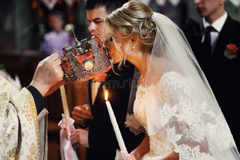 Noiva bonita na coroa de beijo do vestido branco de um padre em nós foto de stock royalty free