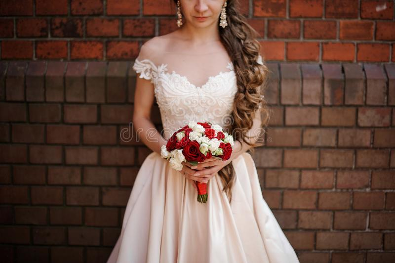 Noiva bonita no vestido de casamento branco com um ramalhete de rosas vermelhas e brancas fotos de stock royalty free