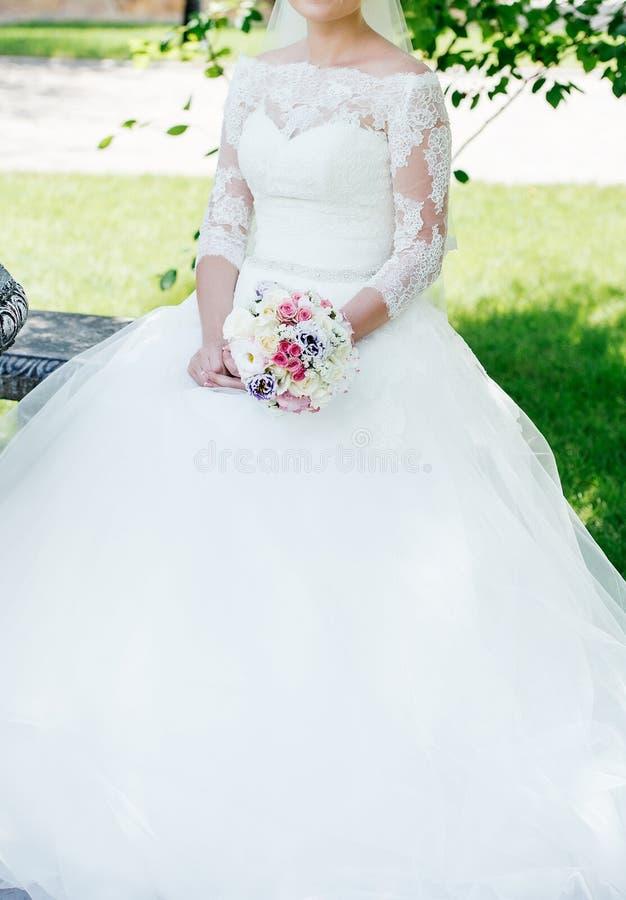 Noiva bonita no vestido de casamento branco do laço com ramalhete do casamento foto de stock royalty free