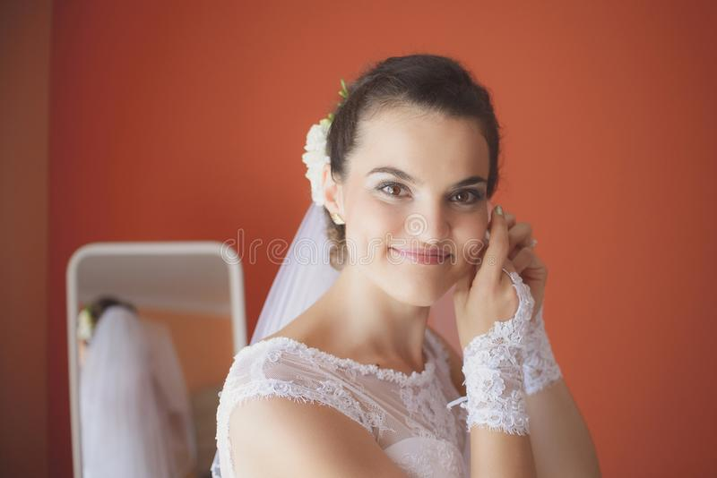 A noiva bonita no vestido de casamento branco põe sobre o brinco fotos de stock