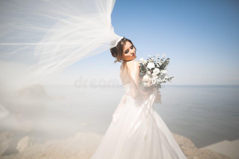 Noiva bonita no vestido de casamento branco que levanta perto do mar com fundo bonito imagens de stock royalty free
