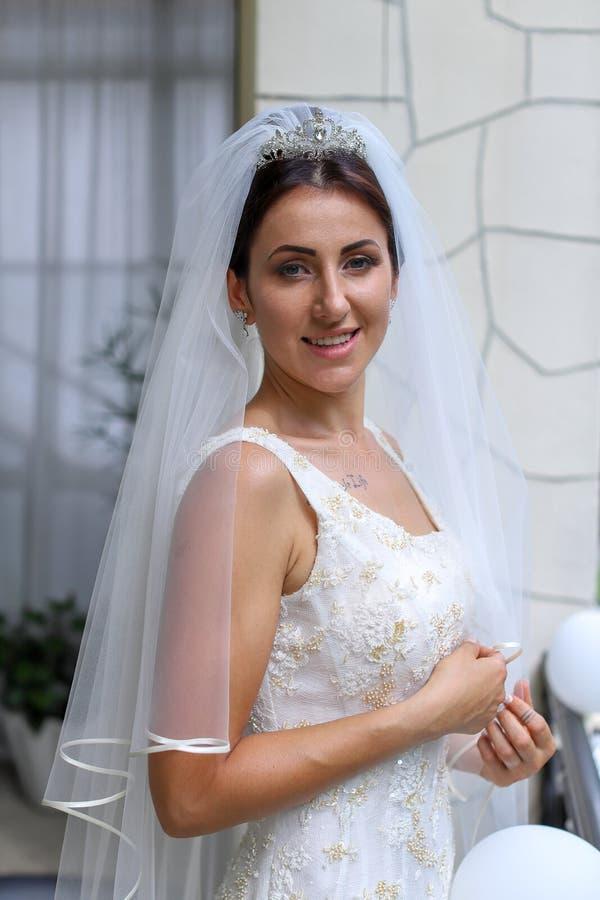 Noiva bonita no vestido de casamento da f?rma A noiva nova impressionante est? incredibly feliz Dia do casamento Uma noiva bonita fotografia de stock royalty free