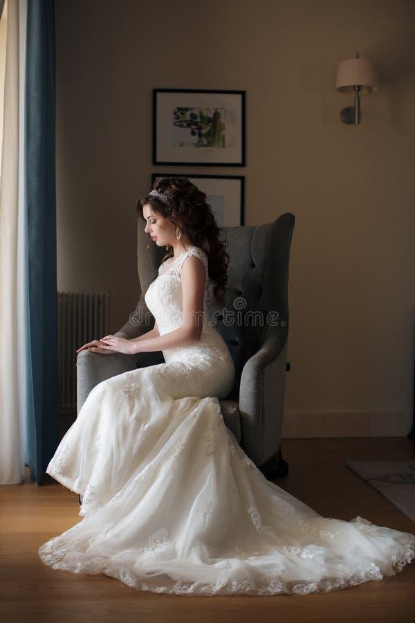 Noiva bonita no vestido de casamento que senta-se em uma cadeira na sala de hotel imagem de stock royalty free