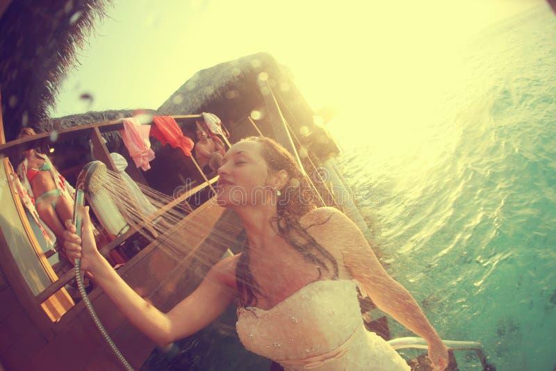 Noiva bonita no vestido de casamento sob o chuveiro em Maldivas foto de stock