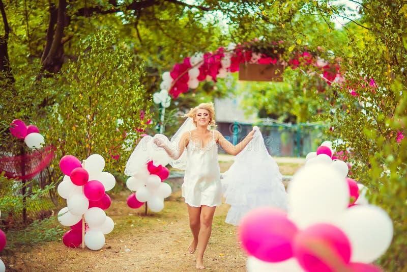 Noiva bonita no vestido de pingamento de seda que corre com os pés descalços a seu vestido de casamento, espaço livre Preparação  fotos de stock royalty free