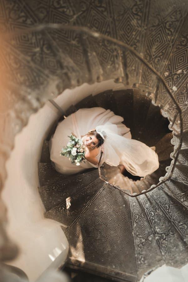 A noiva bonita no vestido magnífico está apenas em escadas foto de stock royalty free