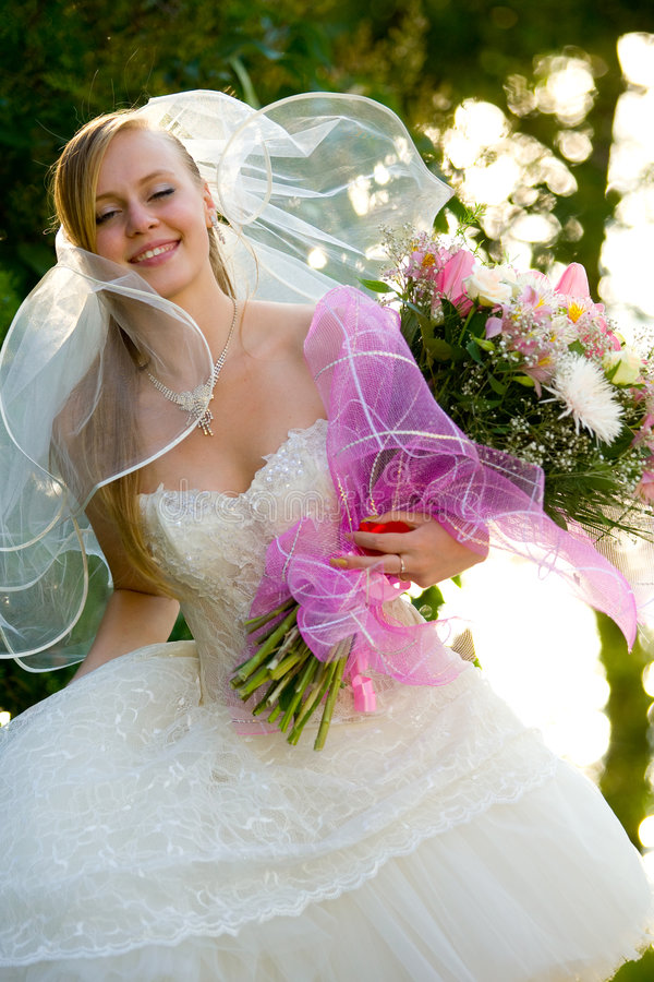 Noiva bonita nova com as flores ao ar livre fotografia de stock royalty free