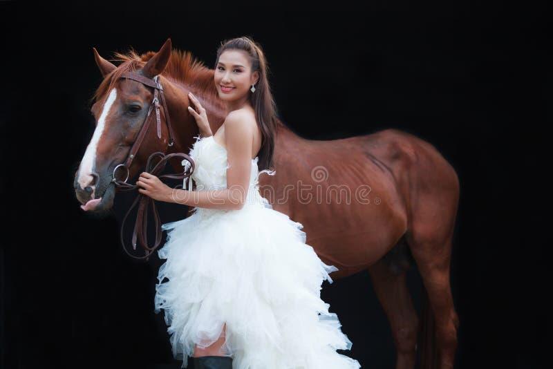 Noiva bonita nova da beleza no suporte nupcial branco do traje do casamento da forma pelo cavalo considerável no fundo preto imagem de stock royalty free