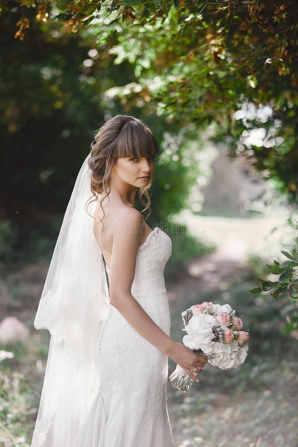 A noiva bonita nova em um vestido elegante est? estando no campo perto da floresta e est? guardando o ramalhete foto de stock