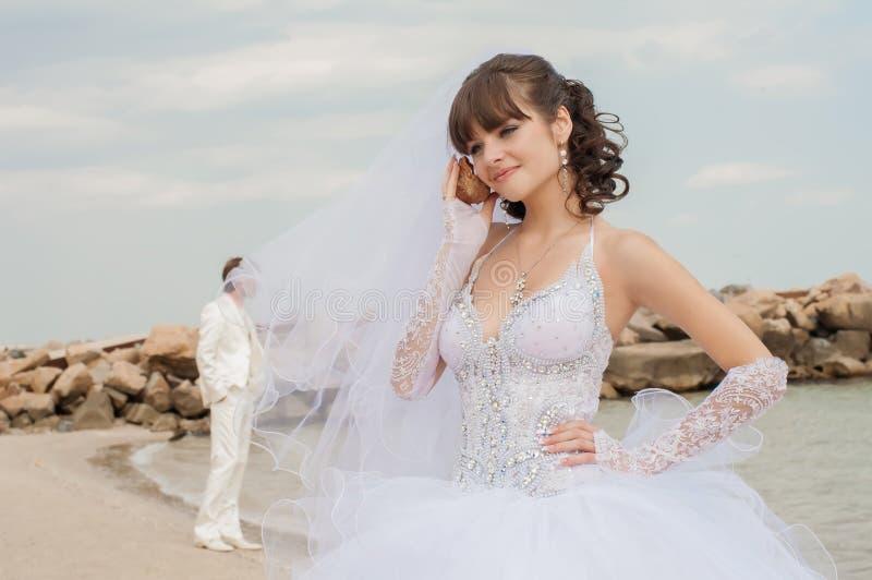 Noiva bonita nova na praia com concha do mar fotos de stock royalty free