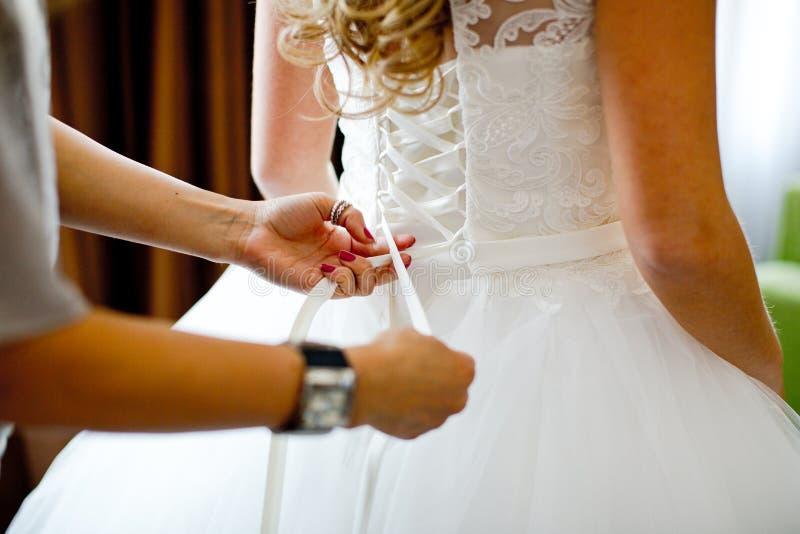 Noiva bonita que amarra acima de seu vestido de casamento imagens de stock