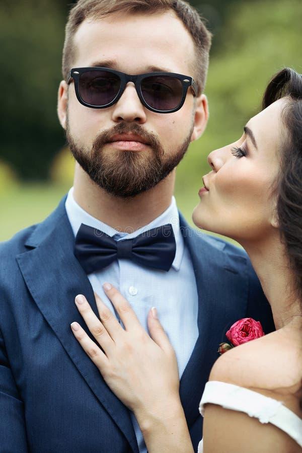 Noiva bonita que inclina-se dentro para beijar o noivo seguro considerável em s fotos de stock royalty free