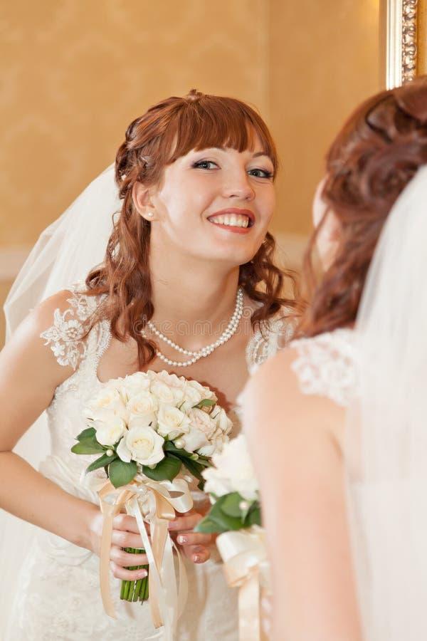 Noiva bonita que olha através do espelho imagem de stock