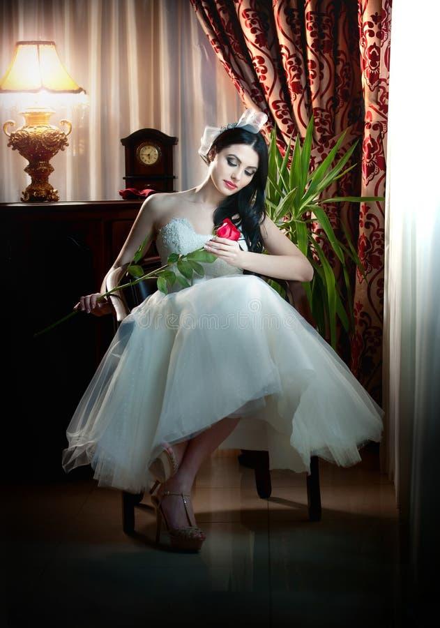 Noiva bonita que senta-se guardando uma rosa vermelha no cenário clássico fotografia de stock royalty free