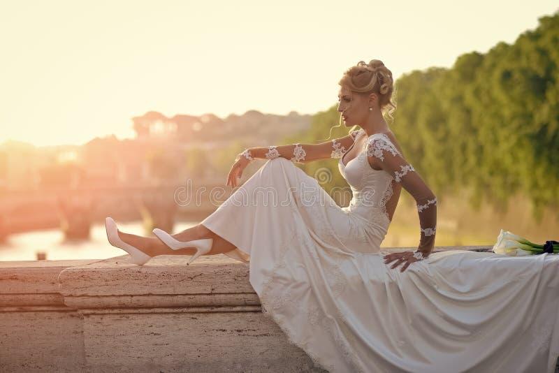 Noiva bonita que senta-se na ponte foto de stock