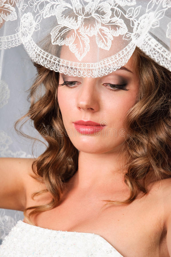 Noiva bonita sob o véu que levanta no estúdio imagens de stock royalty free