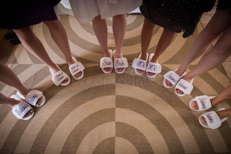 Noiva com as meninas nas sandálias nupciais agradáveis, pés da noiva fotos de stock royalty free