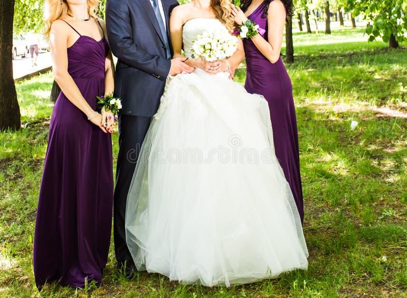 A noiva com noivo e as damas de honra aproximam árvores imagem de stock