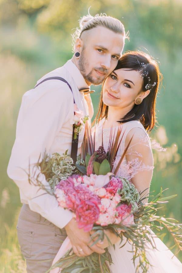 A noiva com os accessoties do cabelo e o noivo do moderno-vestido estão guardando e hugginh na floresta imagem de stock royalty free