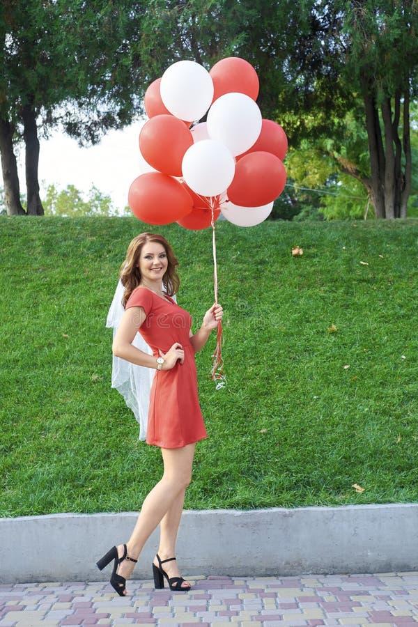 Noiva com os balões que estão no parque imagens de stock royalty free