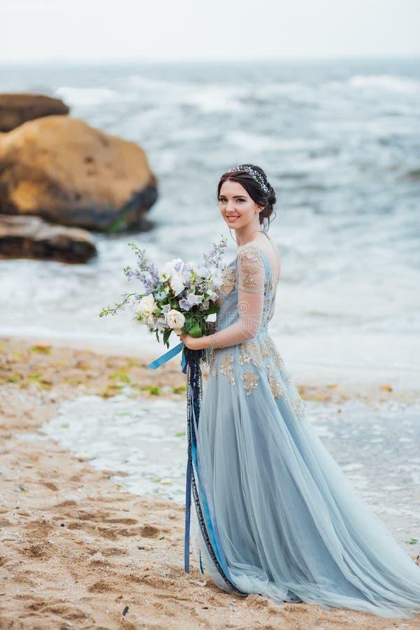 Noiva com um escudo grande na praia fotografia de stock