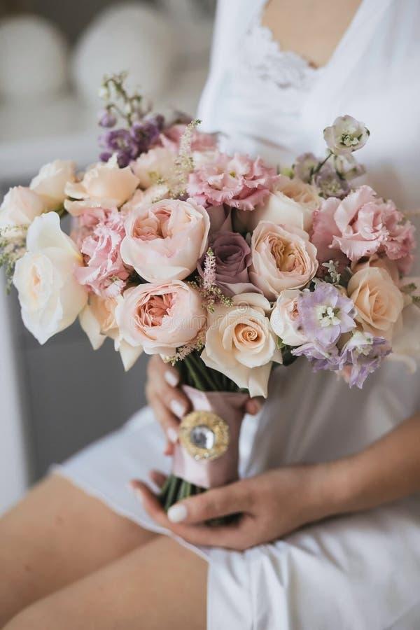 A noiva com uma veste branca realiza em suas mãos um ramalhete delicado do casamento fotografia de stock