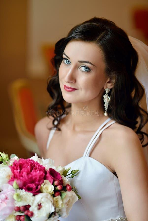 A noiva da beleza no vestido nupcial com ramalhete e o laço encobrem dentro imagem de stock