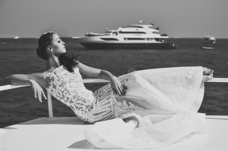 Noiva da mulher no vestido de casamento que relaxa no iate no mar imagem de stock