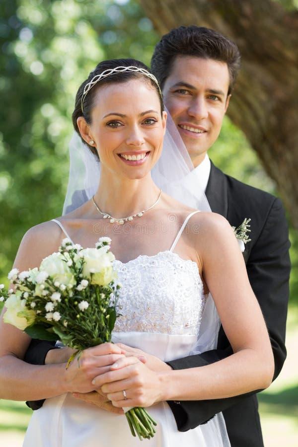 Noiva de abraço do noivo de trás no jardim imagens de stock