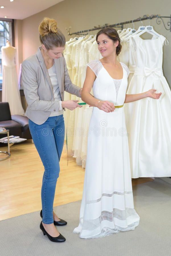 Noiva de ajuda para pôr sobre o vestido de casamento fotos de stock royalty free