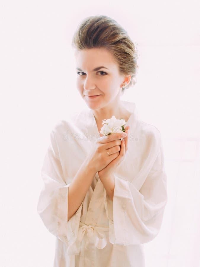 Noiva de sorriso bonita que guarda o mini-ramalhete foto de stock royalty free
