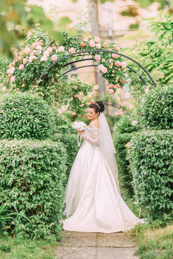Noiva de sorriso bonita que guarda o ramalhete do casamento das rosas brancas no jardim imagem de stock