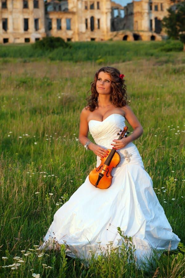 Noiva de sorriso com o violino na frente das ruínas foto de stock