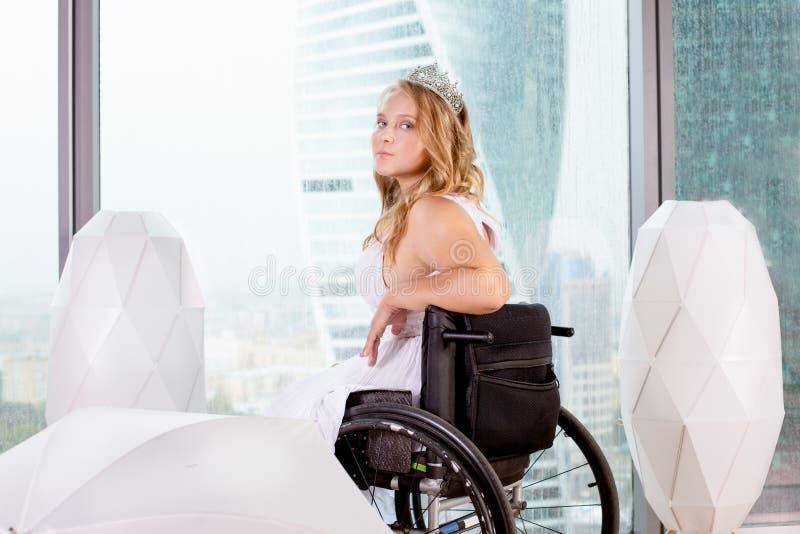 Noiva deficiente bonita que levanta em uma cadeira de rodas na perspectiva de uma janela panorâmico que negligencia os arranha-cé fotos de stock royalty free