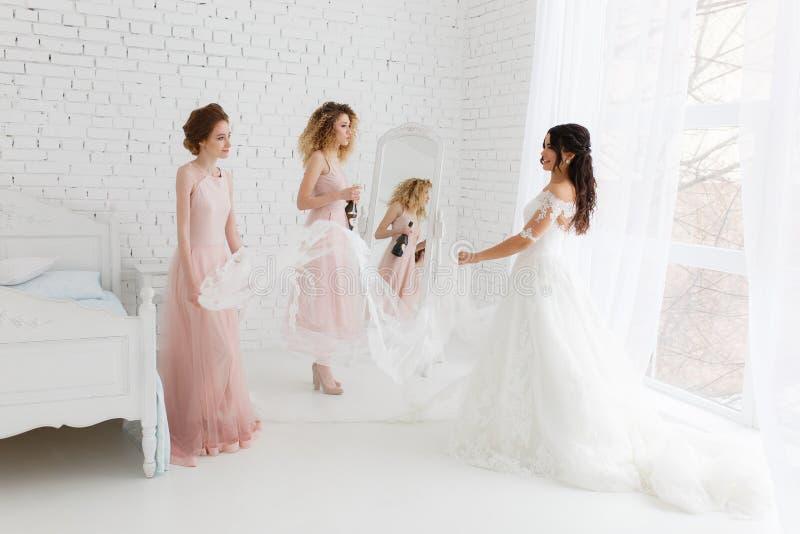 Noiva e damas de honra durante as preparações do casamento no interior branco claro do sótão fotos de stock royalty free