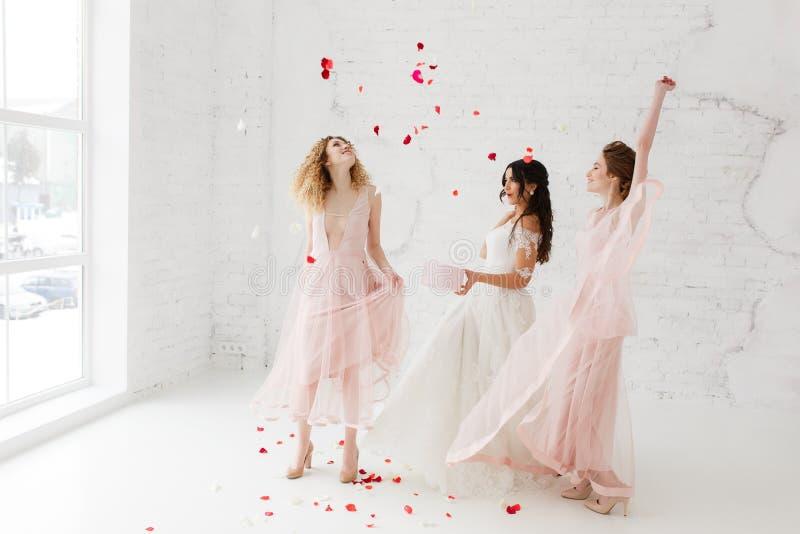 Noiva e damas de honra que dançam no estúdio branco do sótão com pétalas do voo Retrato completo-lenght fotografia de stock royalty free