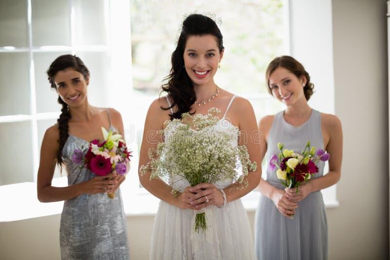 Noiva e damas de honra que estão com ramalhete em casa foto de stock royalty free