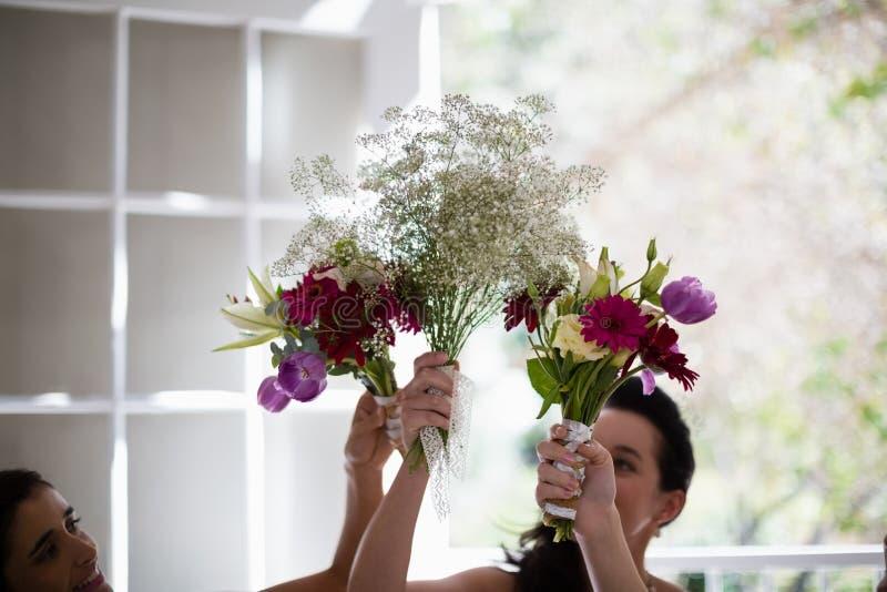 Noiva e damas de honra que guardam o ramalhete da flor em casa imagens de stock