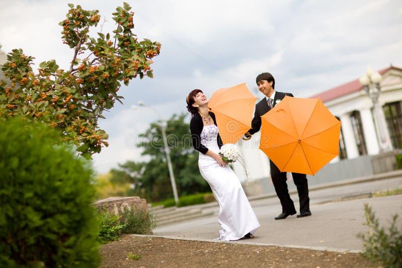 Noiva e noivo com guarda-chuvas alaranjados foto de stock royalty free