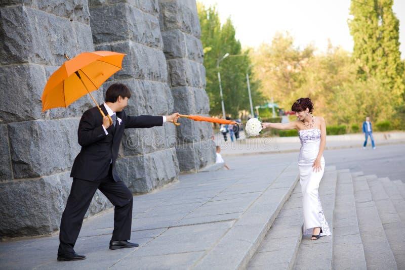 Noiva e noivo com guarda-chuvas alaranjados foto de stock