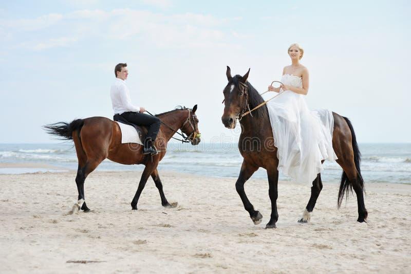 Noiva e noivo no cavalos pelo mar fotografia de stock royalty free