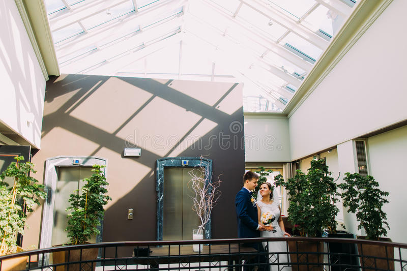Noiva e noivo que olham entre eles Entrada do hotel decorada com as várias plantas exóticas como o fundo imagem de stock royalty free