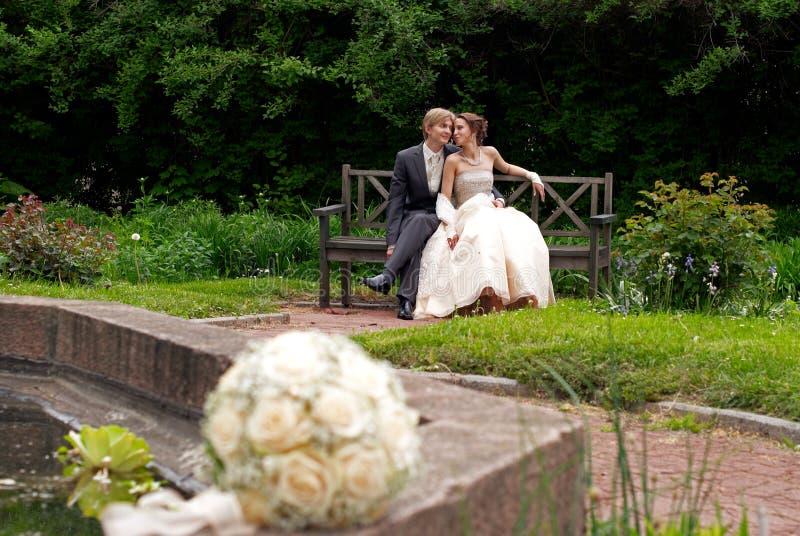 Noiva e noivo que sentam-se no parque fotografia de stock royalty free