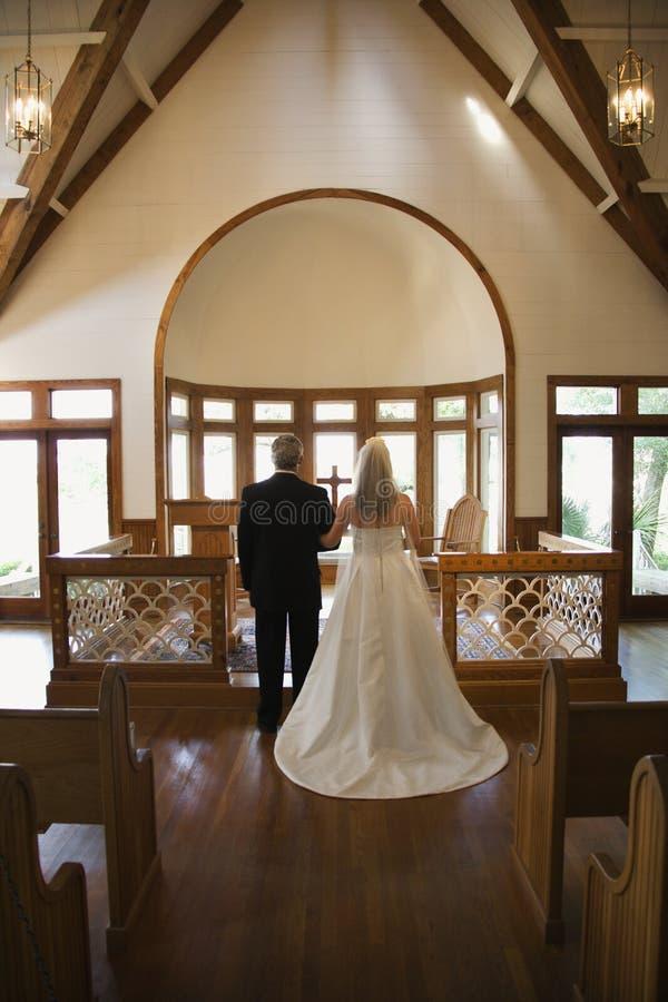 A noiva e o noivo em alteram-se. imagens de stock royalty free