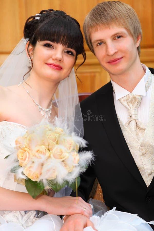 A noiva e o noivo sentam e prendem-se à mão imagem de stock royalty free