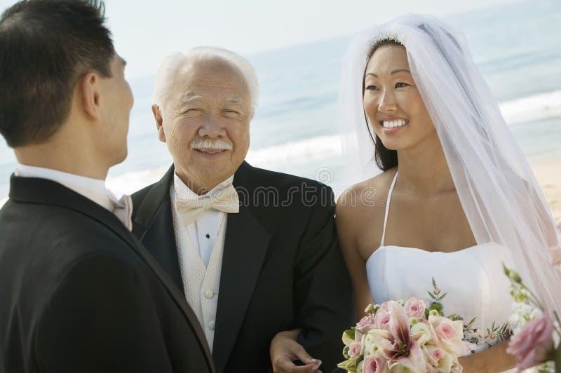 Noiva e pai com o noivo no casamento de praia fotos de stock