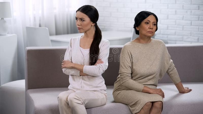A noiva e a sogra na discussão, mantendo o silêncio, sentam-se separadamente e para trás fotos de stock royalty free