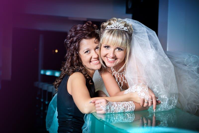 a noiva e sua irmã no dia do casamento estão a barra próxima imagem de stock royalty free