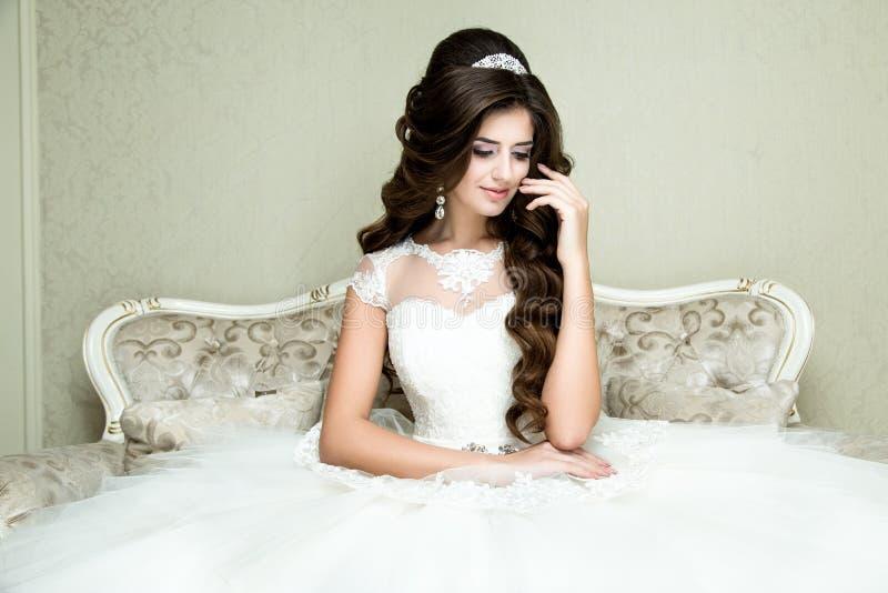 A noiva elegante moreno bonita com composição do casamento e o penteado com diamante coroam o assento na poltrona do vintage foto de stock royalty free